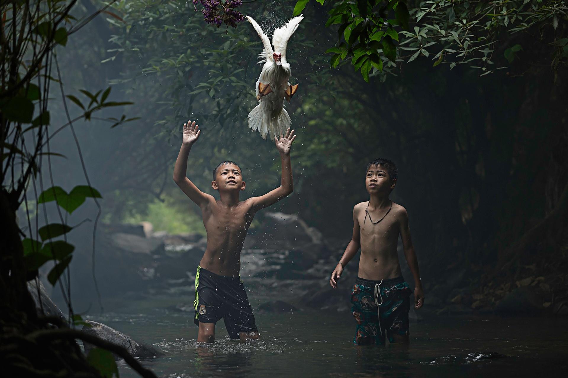 """""""Garotos tentam capturar pato, em cachoeira de Nong Kahi, Tailândia"""", por Sarah Wouters"""